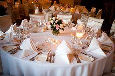 Circular wedding tables candles and rose centrepieces