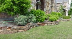 I like the stone border and retaining wall, but not the neat and tidy bushes.