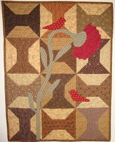 HomeSpunPrims: March 2012: Pieced and applique'd quilt in traditional country colors: tomato red, gold, brown, black, mossy green, featuring spool motifs.