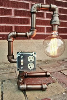 This lovely industrial pipe table lamp is bronze and features an Edison style light bulb. The piece is made with heavy industrial pipes, and may be used as a table lamp or as a wall lamp. Industrial Light Fixtures, Industrial Pipe, Industrial Lighting, Industrial Style, Vintage Industrial, Pipe Lighting, Bedside Lighting, Lighting Ideas, Wall Lighting