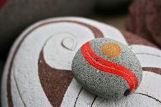 koru hand painted rocks - I really like the bottom, the thick & thin lines don't obscure the rock itself :