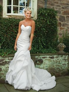 kathy ireland Weddings by 2be Bride Spring 2011 STYLE    E231130 SEASON    Fall 2011 DESCRIPTION    Strapless crinkled taffeta modified mermaid gown with sweetheart neckline, side draped bodice, dropped waist accented with hand-crafted flower and feathers, full bubble pickup skirt with chapel length train. SILHOUETTE    Mermaid NECKLINE    Sweetheart DETAILS    Feathers, floral, pickups FABRIC    Taffeta COLOR    Ivory LENGTH    Floor-length WEBSITE    moncheribridals.com