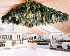 This reception tent is nothing short of epic — a 16 x 16 foot floral canopy comprised of over 14,000 individual stems over top the dance floor, made from a mix of delphiniums, Queen Anne's lace, larkspur, and foraged greens #BridesRealWedding