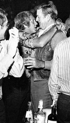 A drunk Steve McQueen hugging a drunk John Wayne, 1970s
