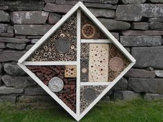 This bee house contains two varieties of bark, wood, straw, bamboo, clay, sub soil, organic soil all aranged in a decorative fashion.