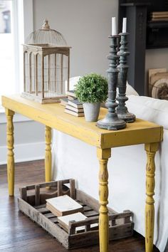 a distressed yellow onsole table will stand out in a grey living room