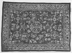 Rug c. 1909. Made of knotted pile in coloured wools on linen warps. Orange background. In the centre and the four corners of the carpet is a motif of a white flower in a circle, surrounded by blue Chinese fretwork. The central motif has more elaborate surroundings. Scattered around these are pictures of boxes, vases and other containers, as well as geometric and plant-based forms. This decoration is in yellow, two tones of blue, white and orange-pink. The border consists of foliage within…