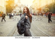 Street portrait of beautiful  young woman walking in city street with backpack.