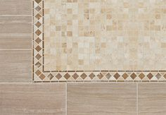 Create the look of slate tile with ceramic tile. Strips of marble subway tile act as a border. Mosaic pinwheels of Carrara marble tiles create a textured rug effect.