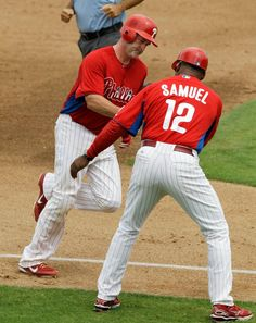 Phillies third base coach Juan Samuel (12) greets the Phillies' Brian Schneider who rounds third after hitting a fifth-inning solo home run off Tampa Bay Rays in Clearwater, Fla., Thursday, March 29, 2012. (AP Photo/Kathy Willens)