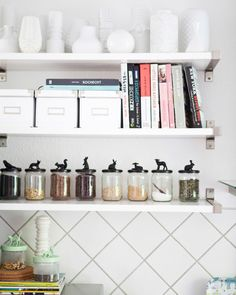 Store customized storage jars on an open shelf with books, vases, and other bits