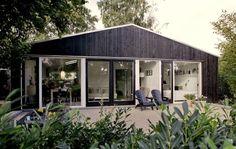 Parcelhuset fra 1960érne havde en kedelig facade, og da huset derudover trængte til efterisolering blev løsningen en udvendig efterisolering og en sort træbeklædning i sortmalet lærketræ. *Træhuse*