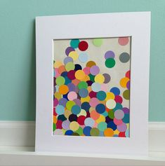 Paint Chip Art: Punch a few circles in paint chips, pepper them on a piece of paper, and frame it for an awesome piece of art. Source: Etsy user ITSBRANNA
