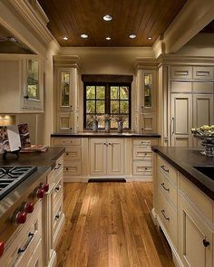 Cream cabinets Dark countertops. beam over window and side cabinets.