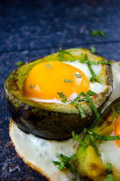 Eggs Baked in Avocado served on a naturally formed white plate. No oven needed! The yolks are perfectly soft unlike the oven baked versions.