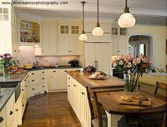 """Love everything about this kitchen ~ the hardware, style and color of the cabinets, the wood countertop on the island with the small attached table at the end, the light fixtures and the sink.  From the Facebook community """"Brambleberry Cottage""""."""