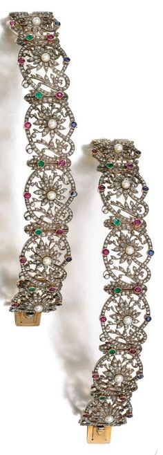 A pair of antique gem set and diamond bracelets, Late 19th Century. Each composed of a series of floral links set with seed pearls, circular-cut rubies, emeralds and sapphires and rose diamonds. #antique #bracelet