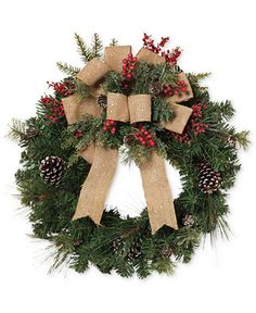"This Gerson pine wreath is a rustic addition to your holiday decor featuring pinecones, berries and finished with a large burlap bow. | PVC/iron wire/polyester/pine cone | Imported | Dimensions: 24"" x"