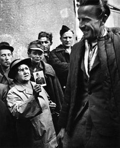 Iconic photos. A mother shows a picture of her son to a returning  prisoner of war, 1947 (This picture about ripped my heart out.)