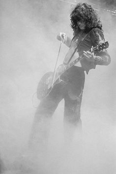 Jimmy Page playing a guitar with a violin bow