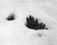 A pair of bound hands and a breathing hole in the snow reveal the presence of the body of a Korean civilian shot and left to die by retreating Communists during the Korean War, Yangji, Korea, January 27, 1951