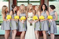 Joyful photo of the bride and bridesmaids, wearing short gray dresses with yellow bouquets - Photo by April Smith & Co.