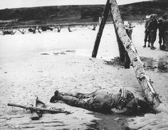 An American soldier, who died in combat during the Allied invasion, lies on the beach of the Normandy coast, in the early days of June 1944. Two crossed rifles in the sand next to his body are a comrade's last reverence. The wooden structure on the right, normally veiled by high tide water, was an obstruction erected by the Germans to prevent seaborne landings. #
