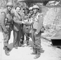 A French civilian greets British troops in La Brèche d'Hermanville. The 3 CMPs (Corps of Military Police) despatch riders are from No. 5 or 6 Beach Group, attached to 3rd Division. (June 6, 1944). Source: Imperial War Museums, # B 5028.