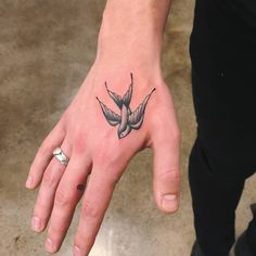 Swallow tattoo on the hand, and little 8 tattoo on the right middle finger on Shawn Mendes.