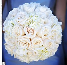 A mostly white arrangement of roses and hydrangeas popped against the bridesmaids' blue dresses.