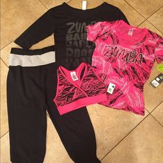 Zumba NWT bundle of 4 size XS/S NWT bundle includes a pair of terry Capri pants XS An 3/4 length sleeve top XS 1 sports bra size S  A pink shirt size XS Tags attached no flaws Zumba Other