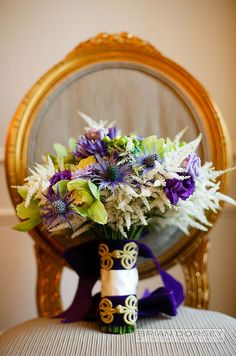 This wedding bouquet of blue thistle, orchids and white astilbe is wrapped in purple ribbon.