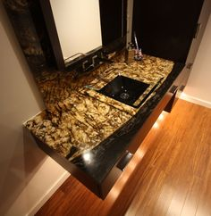 Wall mount vanity with exotic granite counter and glass vessel bowl Powder Room Lighting, Room Wall Tiles, Ceramic Undermount Sink, Floating Sink, Wooden Cupboard, Stainless Steel Faucets, Modern Powder Rooms, Black Granite Countertops, Powder Room Design