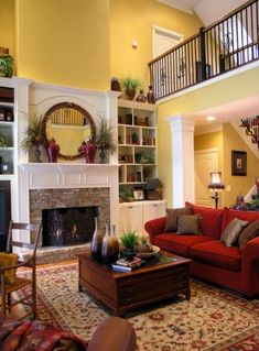 Yellow walls and red sofa- Formal Living Room, Two-story living room with fireplace and built-ins. Balcony above overlooks the room. Winter Living Room, Living Room Decor Cozy, Living Room Red, Living Room With Fireplace, Formal Living Rooms, Living Room Sofa, Apartment Living, Yellow Walls Living Room, Yellow Family Rooms