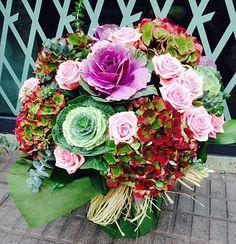 Jarrón con flores en tonos rojos, rosas y verdes