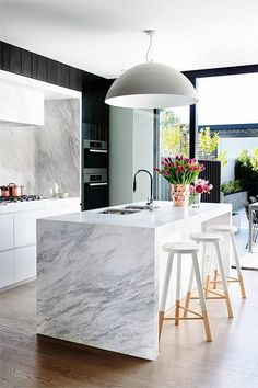 Stylish black and white kitchen. In this kitchen, the black and white contrast has been maintained throughout the décor, including the marble waterfall countertop. The light fixture and the custom made stools infuse this kitchen with a stand out sense of stylish and glamour.