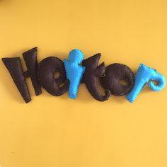 Enfeite de feltro com nome para porta de maternidade ou quarto de criança, costurado à mão e com fita de cetim para pendurar.    Cada letra tem aproximadamente 10cm de largura por 12cm de altura. O nome inteiro mede 40cm de largura.    O preço indicado é para 6 letras com 2 cores de feltro, para ...