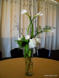 Tall centerpiece with white calla lilies, white hydrangea, roses, curly willow, aspidistra leaves and ruscus. Tropical Centerpieces, Wedding Centerpieces, Tall Centerpiece, Wedding Decorations, Cylinder Centerpieces, Calla Lily Centerpieces, Wedding Ideas, Centerpiece Ideas, Seating Arrangement Wedding