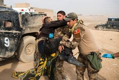 The Ongoing Battle for Mosul - Frontline medics help carry an Iraqi soldier hit by sniper fire at an Iraqi Special Forces 2nd division outdoor field clinic in the Samah neighborhood of Mosul on November 15, 2016