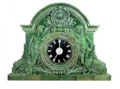 """Originally installed in the Union Depot train station in Troy, New York, this clock was part of the renovation to the third version of the terminal completed in the early 1900s. The clock is fashioned in white terra cotta, glazed in an emerald green, and divided into sections. A Grecian style relief surrounds the 30"""" clockface. On each side of the face, there is a youth and above is a locomotive breaking through a tunnel of steam.   H 88"""" x W 122"""" x D 18"""""""
