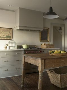 Rafe Churchill 1929 Connecticut Farmhouse Kitchen | Remodelista. grey cabinets with brass hardware, farmhouse table.