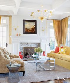 The living room of this home in the Hamptons takes on a more contemporary aesthetic with a glass-topped coffee table from Holly Hunt, vintage side table and gold Murano glass chandelier and sconces from Lunardi Group. Interior Design by Nanjoo Joung and Rick Garofalo, NR Design Studio. #gold