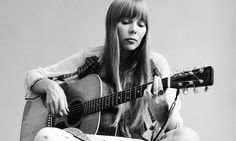 Portrait of Canadian musician Joni Mitchell seated on the floor playing acoustic guitar, November 1968. This image is from a shoot for the fashion magazine Vogue. Mitchell wears a loose-fitting white dress. (Photo by Jack Robinson/Getty Images)