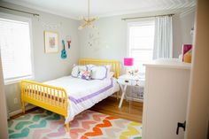 Jenny Lind yellow bed, Land of Nod heart rug, bedding, curtains and desk. Ikea dresser. West Elm light. Caitlin Wilson pillow. Bright and colorful!