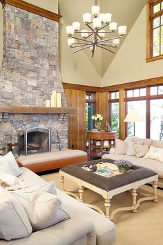 Beige Living Room with Stone Fire Place containing: Classic Style Coffee Table with Gray Sofa also Wooden Bench Frame plus Textured Area Rug together with Milky Glass Chandelier with Varnished Window Frame also Reclaimed Wood Shelf plus Rounded Accent Table