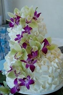 Three tier white chocolate shavings wedding cake decorated with purple dendrobiums and green cymbidium orchids.
