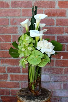 Cool arrangement with callas, orchids, anthurium, and monstera leaves