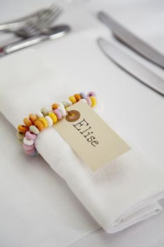 Using candy necklaces as a napkin holder and place marker is a great idea for a kids party or maybe a little girls tea party.