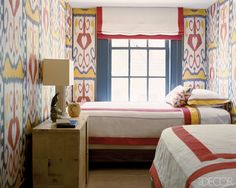 A compact guest bedroom makes a big impact in the West Village townhouse of Steven Gambrel and Chris Connor thanks to walls sheathed in a vintage Uzbek ikat. Simple, elegant bed linens complement the bold treatment.