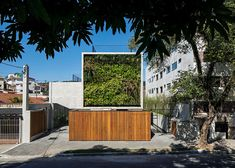 A square wall covered in plants announces the presence of this concrete housing block in São Paulo.